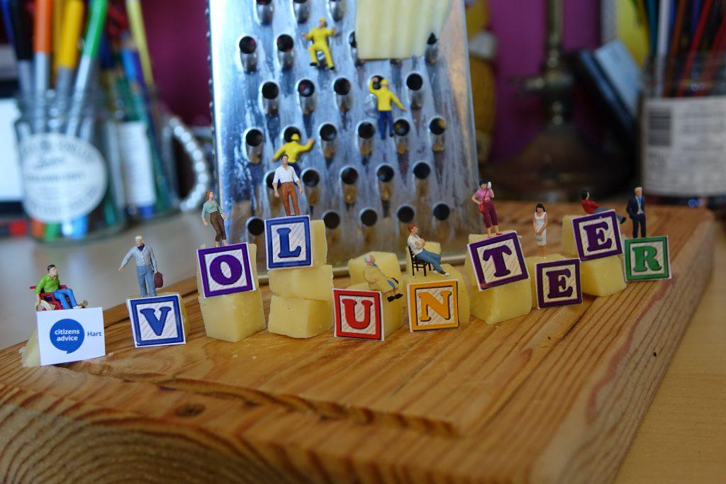 Citizens Advice Hart's Volunteer image, with small figurines on blocks of cheese