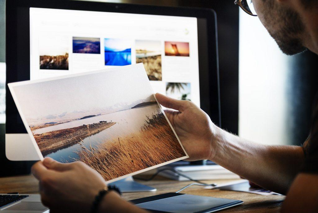 Man sitting at desk looking at landscape photo