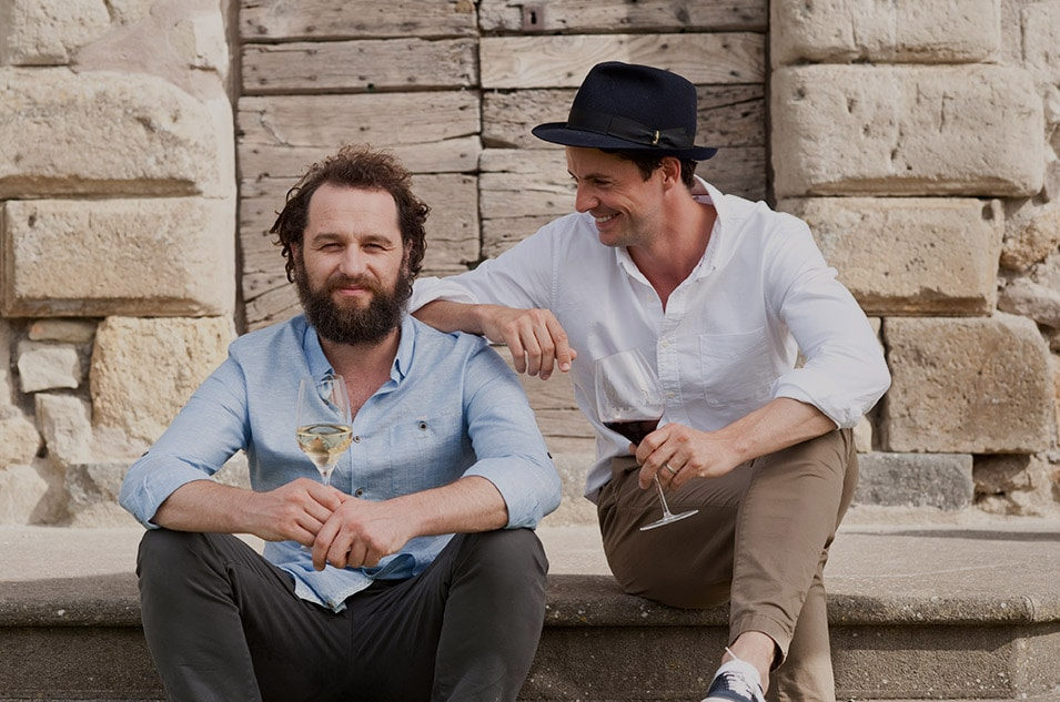 Matthew Rhys and Matthew Goode sitting on a step drinking wine and laughing